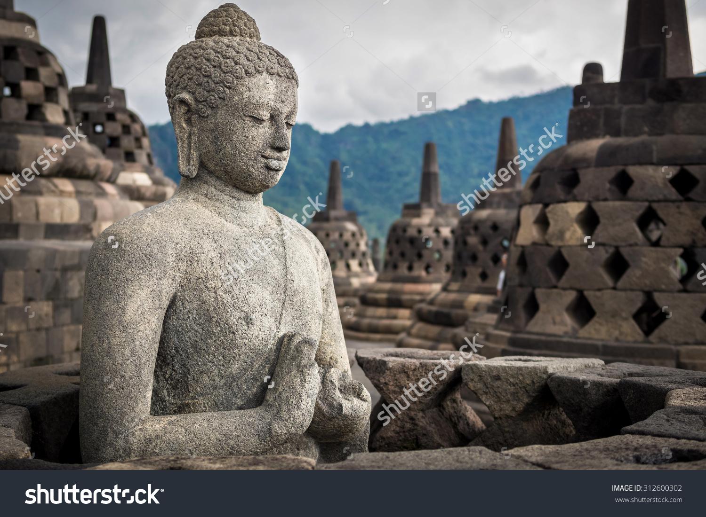 stock-photo-ancient-buddha-statue-at-borobudur-temple-in-yogyakarta-java-indonesia-312600302